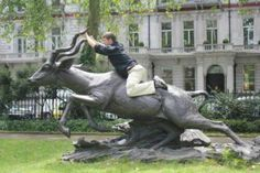 24 Hilarious Pics Of People Posing With Statues: Riding A Magnificent Beast