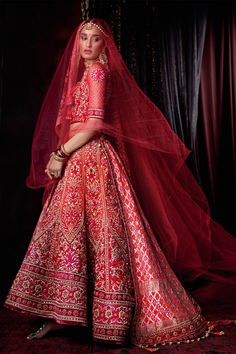 A zardozi embroidered graded bridal lehenga and red wedding veil