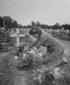 Simone Renaud, wife of the Mayor of Sainte-Mère-Église France, pictured in July 1944, placing flowers on one of the graves of U.S. soldiers she has adopted, that belonging to General Theodore Roosevelt, Jr, he died of a heart attack on July 12, 1944  From the LIFE Magazine Archives - Ralph Morse Photographer