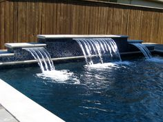 Sheer Decent Water Fall on Deep Blue water delivering curtain of water. A Dolce build pool in Dallas/Fort worth area. Dazzling glass tile veneer on this raised wall with sheer water features.