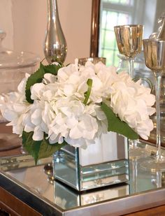 Love white flowers in mirrored vases...