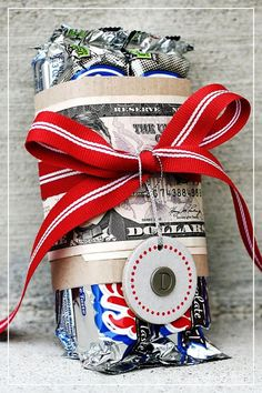 """<p>Add a little weight to your package by wrapping a bill around some candy bars. This is the real """"fun size."""" As an extra touch, why not use 100 Grand bars instead of 3 Musketeers? <i>(Photo: <a href=""""http://simplyjstudio.blogspot.com/2011/06/quick-gifts.html"""">Simply J Studio)</a></i></p>"""