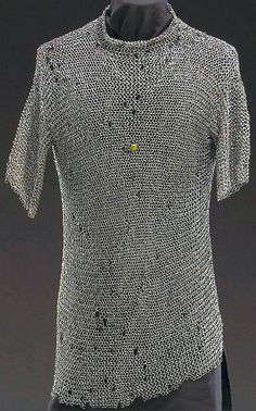 European (German) riveted mail hauberk, 2nd half of the 15th century, mid thigh length shirt with short sleeves coming to just above the elbows and stand-up collar of heavier links. Composed of riveted links of round section, the chest with brass button stamped with the Nuremberg mark with the legend Stadt Nurmberg in Gothic miniscules. Condition: Showing some scattered holes and losses. Rear lower edge missing 3 inch x 20 inch section. Length: 32 inches. Weight: 11 pounds.