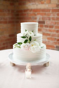 three tiered white wedding cake before exposed brick