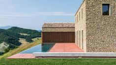 GGA Architects has transformed the site of an old hilltop settlement in Italy's Marche region into a contemporary house comprised of stone structures.