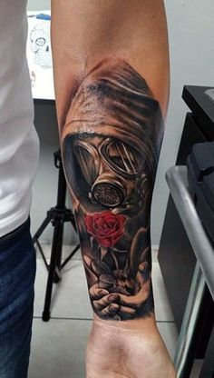 Guys Wrist Tattoo Of Man In Gas Mask Holding Red Color Rose Flower