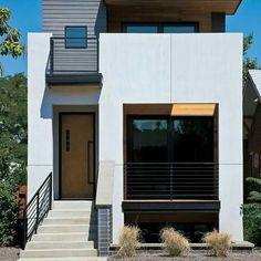 Casa com escada, varanda frontal e acabamento branco.