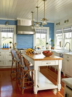 Honed stone countertops lend polished 1930's charm to this coastal kitchen. Blue recycled glass backsplash in a running bond pattern not only makes a statement but is easy to clean and extremely durable. (Photo: Tria Giovan)
