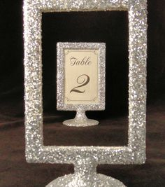 Picture Frame Table Number Holders Silver by MariesBlingNThings, $50.00.  I think we can DYI on this