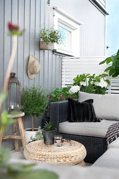 SOMMER I LUFTEN: Det er mye man kan gjøre for å skape hygge på uteplassen. Også når uteplassen er liten. Her er det pyntet med grønne vekster, lykter og fine krukker. På veggen henger en sommerlig hatt. Bordet er to puffer fra Ikea.