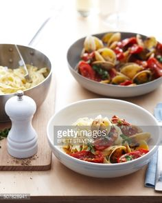 Stock Photo : Bowls of fettucine clams with fresh tomatoes and herb garnish
