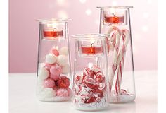 Symmetry Trio Glass Vessels with Votive Cup Candles on Top. Fill the glass vessel with your own decorative accents.