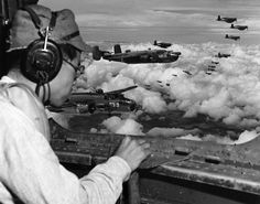 In the waist of a Marine Mitchell bomber Japanese prisoner of war, Second Lt. Minoru Wada, scans the mountains below, picking out landmarks that will aid him on leading other Marine bombers and fighters over the target. Major Mortimer H. Jordan, air strike coordinator, has moved forward into the nose of the bomber to take command immediately as the target is pin-pointed