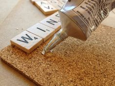 A package of gently used, square edged Scrabble tiles* DIY Scrabble Coasters  You will need: E-6000 glue 1 thin cork board or pre-cut cork coasters Sharp scissors or an X-acto knife Clear Polyurethane spray
