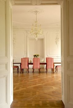 An unexpected ingredient — oversize red gingham upholstery — adds a rustic, homespun note to this grandly proportioned, boiserie-covered dining room. Paris Flat, French Table, Red Gingham, Gingham Check, Interior Decorating, Interior Design, Decorating Ideas, Dining Room Chairs, Dining Rooms