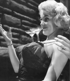 Vintage model June Wilkinson balancing martini glasses on her breasts.