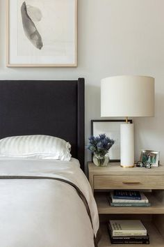 Gold grasscloth wrapped nightstand is designed next to a black wingback bed with white hotel bedding and white silver striped shams.