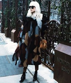 Courtney Trop of Always Judging wears a patchwork coat, cropped pants, heeled oxfords, black sunglasses, and a Chloé Drew saddle bag