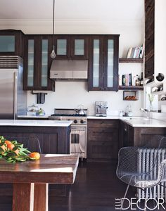 The kitchen cabinetry and island are made of espresso-stained    reclaimed fir, the refrigerator is by Sub-Zero, and the range and vent hood are by Viking;    the sink fittings are by Grohe, and the light fixture is by Rejuvenation. William Waldron  - ELLEDecor.com