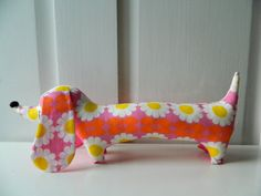 This is from my range of mini Dachshund toys.    Handmade with retro cotton from my own collection, which I designed myself. It has contrasting ear backings and base.    Nose is handmade from felt and the eyes have been chain stitched on by hand. Stuffed with polyester filling.    Measurements (approx):  12x 4 (30cm x 10cm)    Thank you for looking. Please look at my shop for more soft toys.