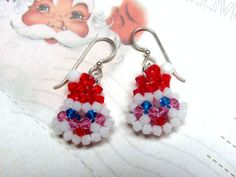 The Santa Claus earrings are made with light siam, capri blue, rose, and white alabaster Swarovski crystal bicone beads, and white alabaster Swarovski crystal round beads for Santas pom-pom. Santa is made by using a two needle right angle weave technique. The Santa face is very small and cute, only approximately 5/8 x 3/4. These earrings are gonna be a big hit at all your Christmas parties. Ho, Ho, Ho!    Jolly St. Nick earrings hang from 20 gauge sterling silver ear wires and meas...