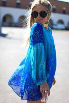 bright blue baby doll tunic, subtle floral print, large john lennon glasses