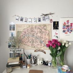 Love the tidy mess of this desk. Flowers bring colour, maps and wall calendar, books and pencils!