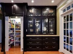 I love the clean sophisticated look of these black cabinets! I love the hidden pantry even more!!! If I ever win the lottery....dreaming!