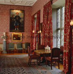 Deep red and gold damask curtains line the windows of the dining room
