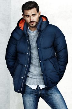 The classic puffer jacket has long been an outerwear essential. Dark blue padded jacket and gray wool-blend sweater. Via H&M.