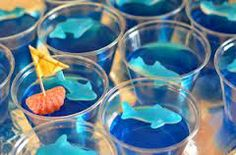 Blue jello in a cup with a gummy shark. Cute!