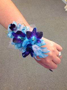 Wrist corsage Blue bomb orchids with silver accents.