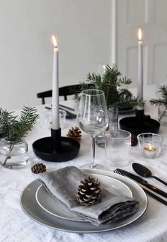 Minimalist Christmas table styling with fir, candles & pine .- Minimalist Christmas table styling with fir, candles & pine cones Minimalist Christmas table styling with fir, candles & pine cones