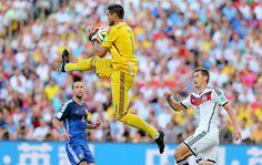 El guardameta argentino Sergio Romero para el balón ante el delantero alemán Miroslav Klose.