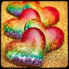 rainbow hearts on gold glitter and lie on each other