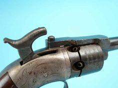 Early Springfield Arms Co. James Warner's Patent Pocket Model Revolver. Serial no. 23F, .28 caliber percussion, 6-shot cylinder with roll-engraved line decoration and 1857 patent marking and maker, Springfield address; 2 1/2-inch round barrel; no address markings visible; scroll engraved frame; blued finish, with case-hardened hammer. Varnished walnut grips.