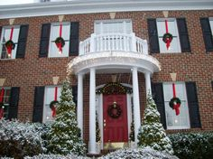 Wreath and a candle in every window, lighted garland and icicle lights on the porch, lights in the hedges