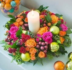 Christmas wreath of clashing pink, red and orange roses, plus berried ivy and baubles. Finished with an ivory church candle. Photo by Clive Nichols and published in the Evening Standard. Design by Judith Blacklock Flower School