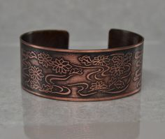 To create this fun bracelet, I started by cutting a length of copper sheet then I transferred the flower pattern onto it and acid-etched the pattern into the metal permanently.