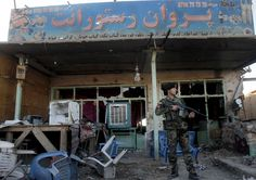 An Afghan soldier stands guard after an attack on an airport.