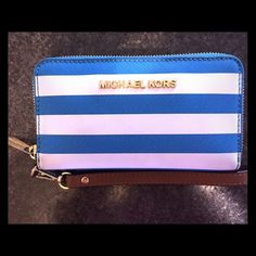 Michael Kors wallet / wristlet Offering less on Merc. Blue and white stripes. I used this daily but I baby my Michael Kors items so this is in excellent condition! No stains scratches or pilling whatsoever the only wear it has is on the gold zipper part shown in the picture Michael Kors Bags Wallets