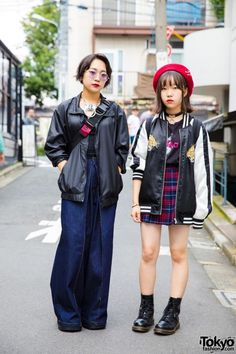 Haneul (at the right) is wearing a black t-shirt from Joyrich under an embroidered Japanese souvenir jacket (sukajan), a plaid skirt from American Apparel, and boots from Dr. Martens. Her accessories – some of which are from Style Nanda – include a red beret, an O-ring choker, and a black backpack from Thrasher At the left, Rico's outfit features a black top from American Eagle underneath a black jacket from Kobinai, wide leg jeans from Faith, and platform boots from Demonia.
