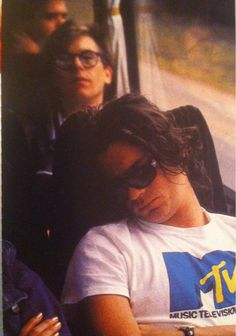 Michael Hutchence sleeping an MTV t-shirt with Kirk Pengilly behind him on the tour bus.