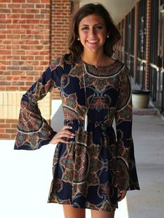 This navy paisley print short dress features long bell sleeves and a shirred empire cut waist. Designed and manufactured in the US! Fabric Content: 50% COTTON 50% POLYESTER [Model is wearing a size sm