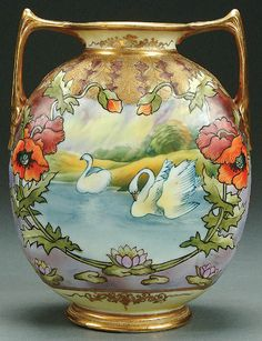 A NIPPON SWANS IN LAKE MOLDED SCENIC PORCELAIN HANDLED VASE CIRCA 1920 WITH HAND PAINTED SWANS FRAMED IN A FLORAL CARTOUCHE OF POPPIES AND WATER LILIES BELOW AN EMBOSSED LEAF FORM SHOULDER