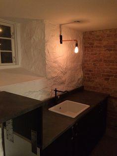 Tvättstuga i källare. Putsen bortknackad på ena väggen så att teglet kom fram. Rent betonggolv.