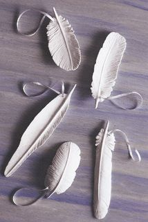 make your own all you need is some clay and a toothpick (one of those metal ceramic probe thingies would probably work better but i think i left mine in storage...).  start by taking a small piece of clay and flatten it in the shape you want your feather to be in.  i started by tracing where i wanted the center quill of the feather to be and pressed down everywhere else so that the quill was the only raised area.  then just use your toothpick and make lines down on either side of the quill.  it'