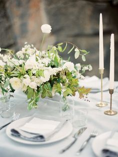 white and green centerpiece and pale blue tablecloth