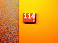 Collegio Universitario Einaudi, sezione Po, ristrutturazione dell'architetto Luca Moretto. Dettaglio di una porta e del numero identificativo di una camera del piano arancione (ogni piano ha un proprio colore di riferimento). www.lucamoretto.it