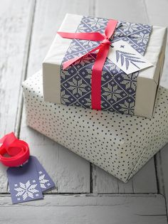 love this needlepoint wrapping paper in blue and white paired with white paper with blue polka dots and a red ribbon.